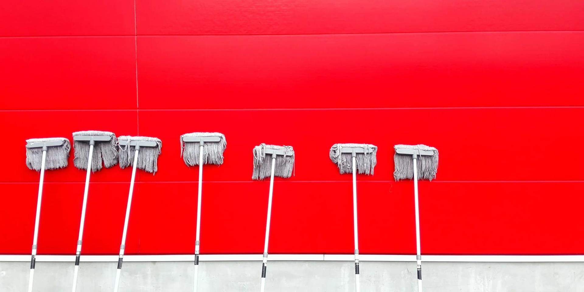 Seven mops leaning against a red wall